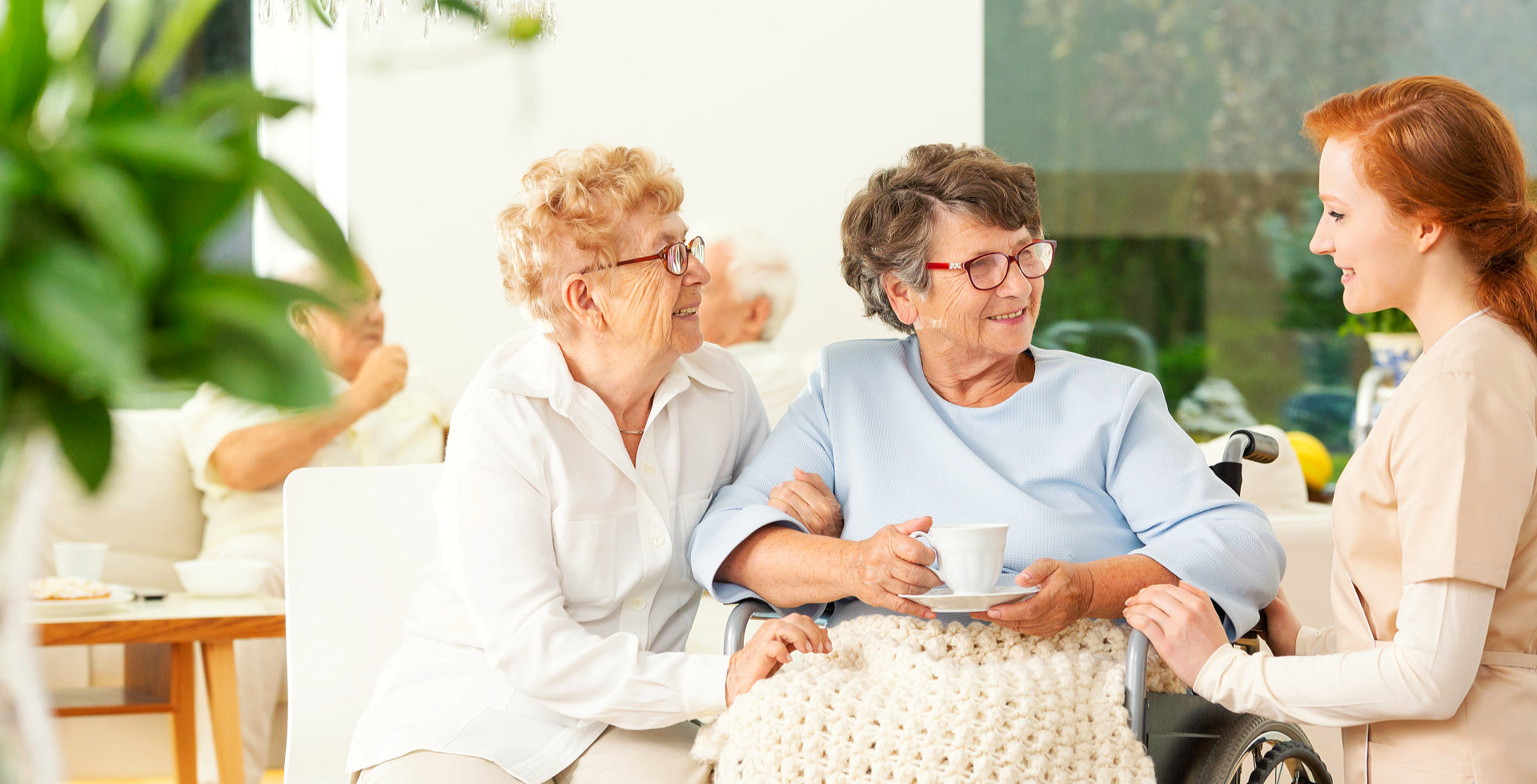 caregiver talking to two senior women