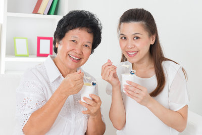 senior woman and young woman eating food