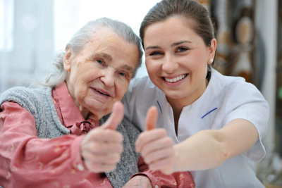 senior woman and nurse are showing thumbs up