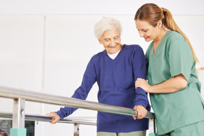 physiotherapist helping old senior womanon theraphy